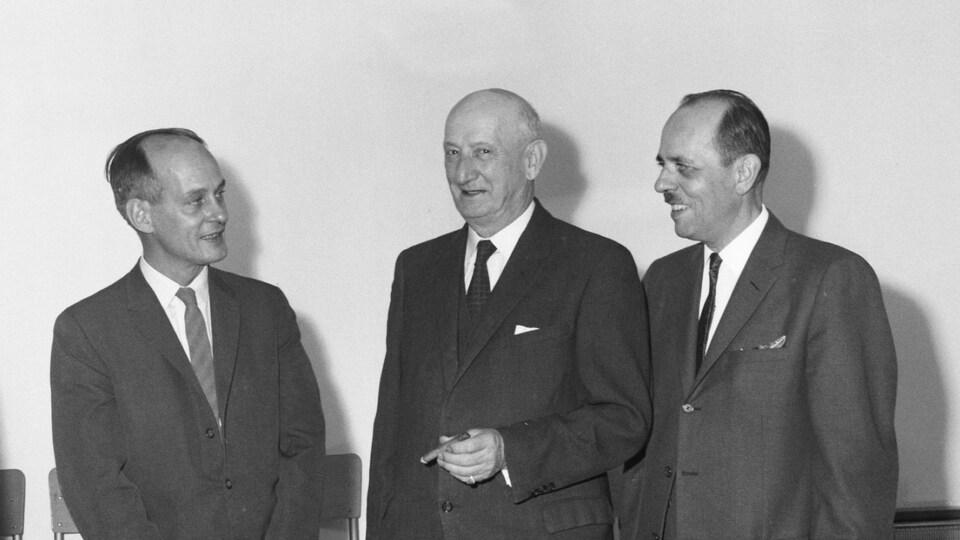 Trois hommes en complet dans une photo en noir et blanc.
