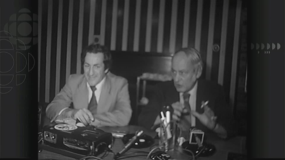 Deux hommes discutent à une table.