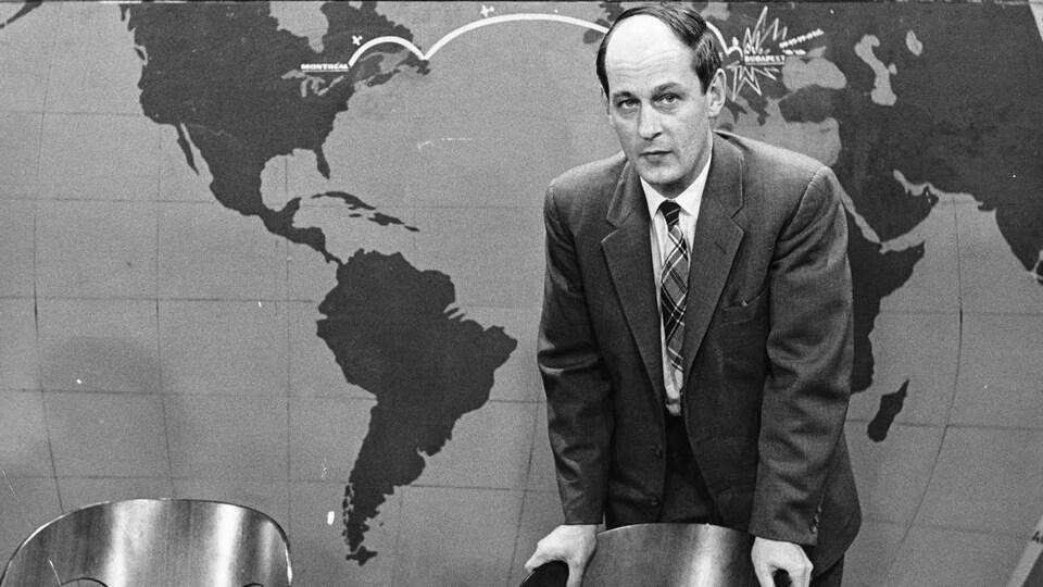 Debout devant une carte du monde, l'animateur René Lévesque est appuyé au dossier d'une chaise, une cigarette entre les doigts.