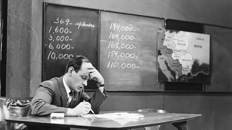 Assis à une table, l'animateur René Lévesque consulte les documents devant lui en se tenant le front d'une main. Derrière lui, accrochés au mur, il y a un tableau chiffré et une carte de l'Europe.