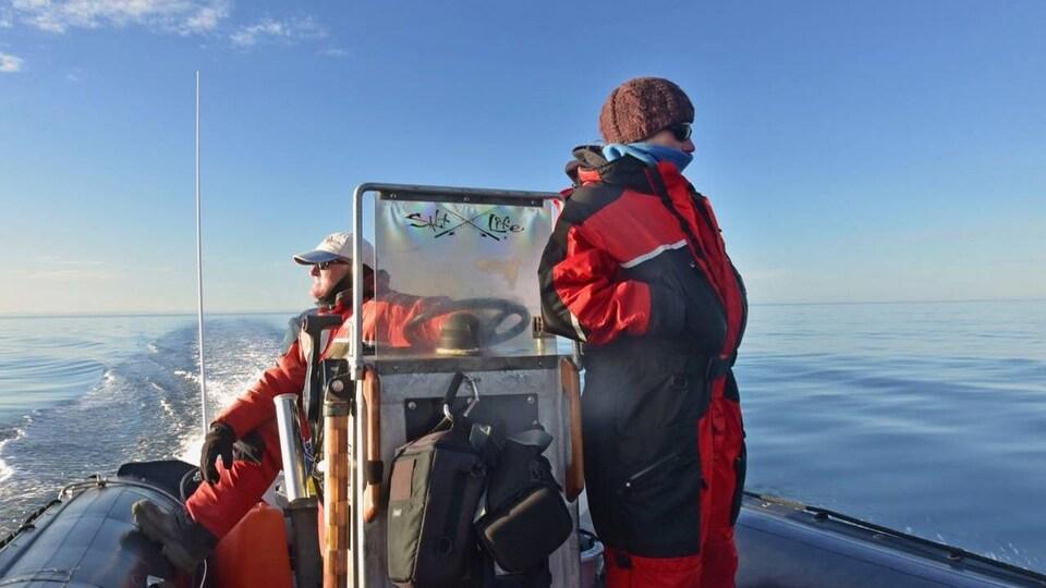 René Roy et une scientifique regardent au large, chacun de leur côté de l'embarcation.