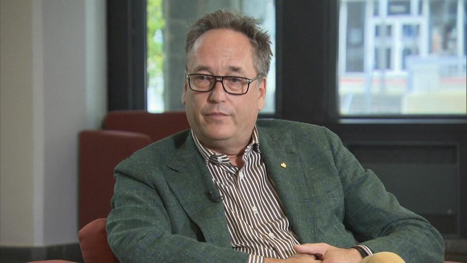 René Villemure assis dans un fauteuil durant une entrevue.