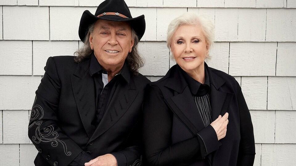 Les deux artistes sourient et sont portent des vestons. Paul Daraîche porte un chapeau de cow-boy.