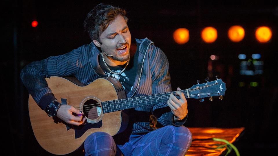 Un jeune homme joue de la guitare sur une scène.