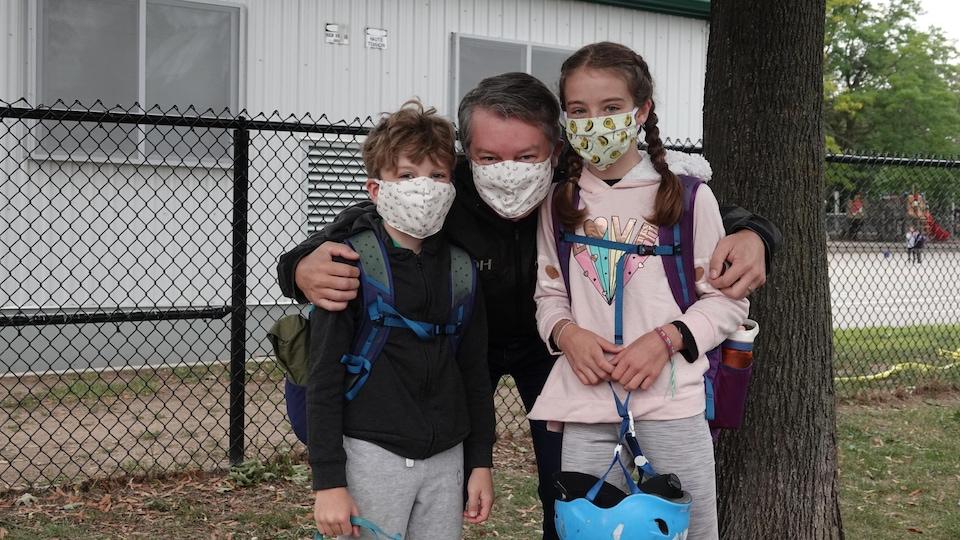 Esmée, Félix et leur père posent avec leurs masques devant la clôture de l'École élémentaire Pierre-Elliott-Trudeau à Toronto.