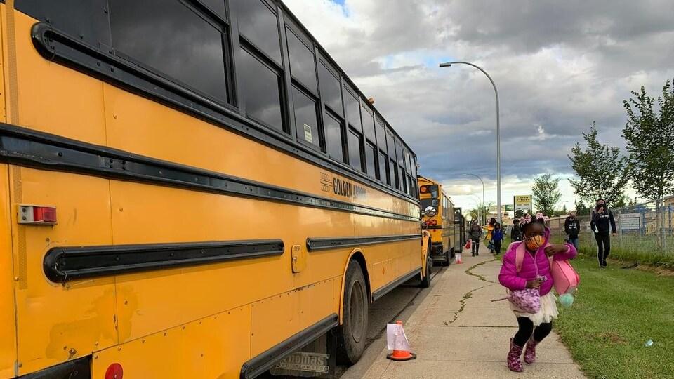 Une élève vient de descendre d'un bus scolaire.
