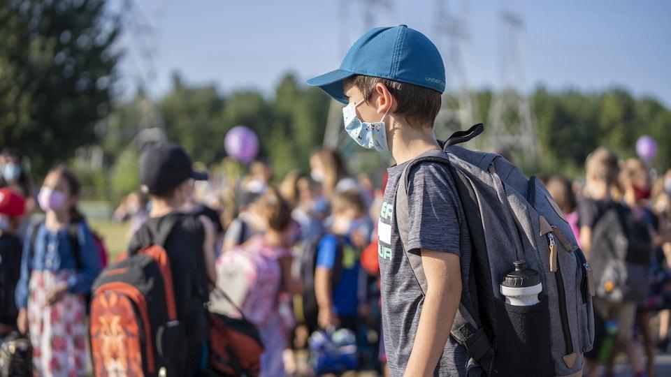 Un élève masqué devant de nombreux élèves dans une cour d'école.