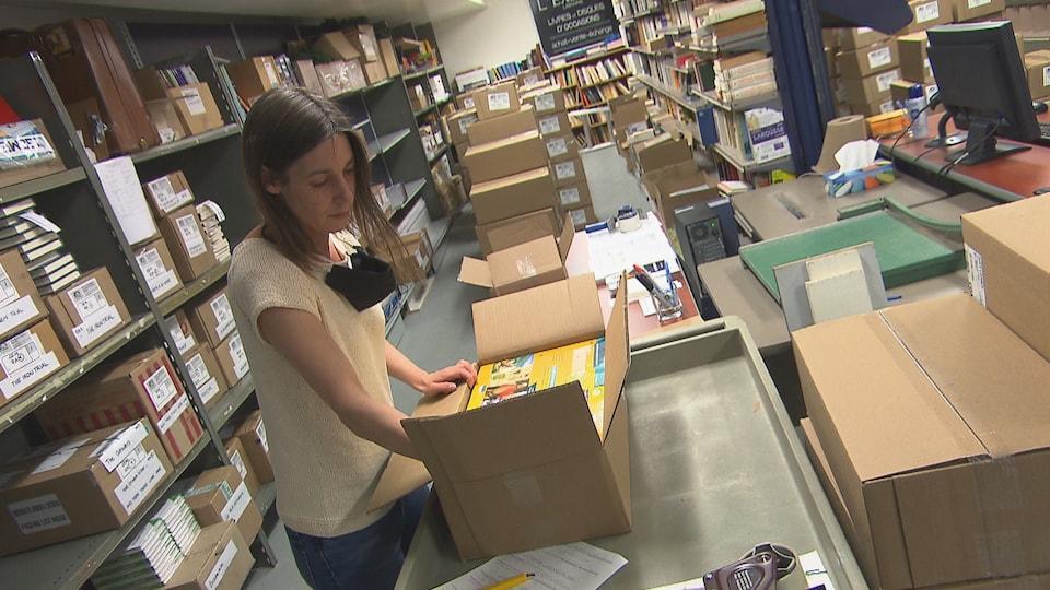 Une femme est en train de placer des livres scolaires dans une boite.