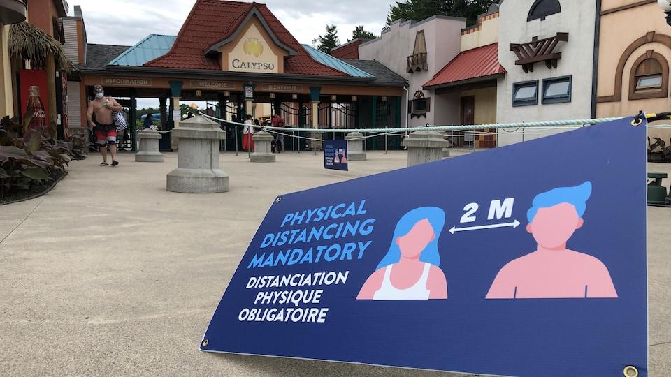Un panneau indiquant de garder une distance de deux mètres à l'entrée d'un parc aquatique.