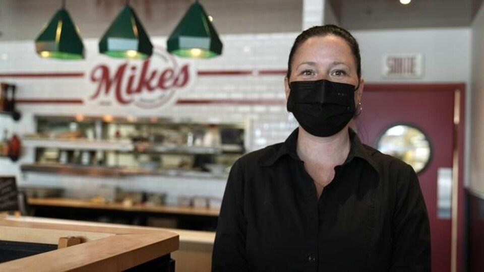 Une femme portant le masque regarde la caméra, dans un restaurant.