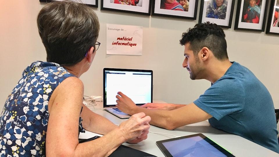 Un jeune homme tape sur le clavier d'un ordinateur portable tandis qu'une dame plus âgée l'observe.