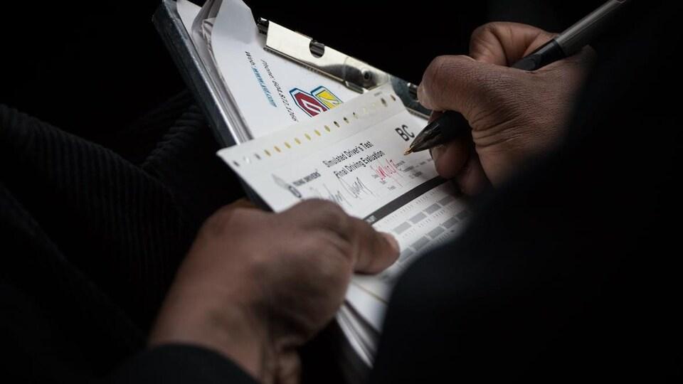 Un évaluateur prend des notes pendant un examen pratique.