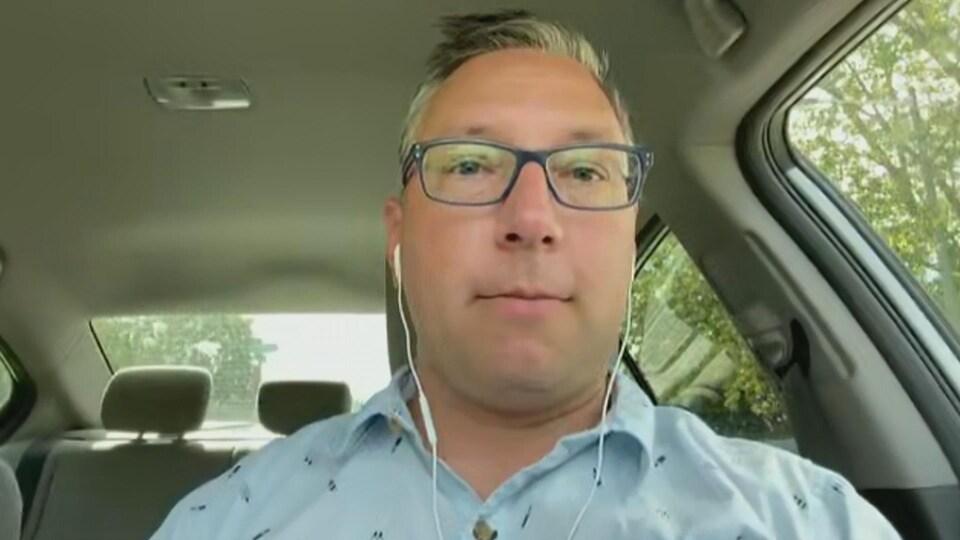 Un homme dans sa voiture, pendant une entrevue menée par visioconférence.