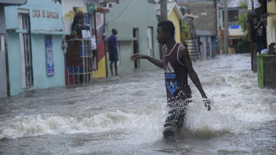 Un homme marche dans une rue inondée de Santiago, en République dominicaine