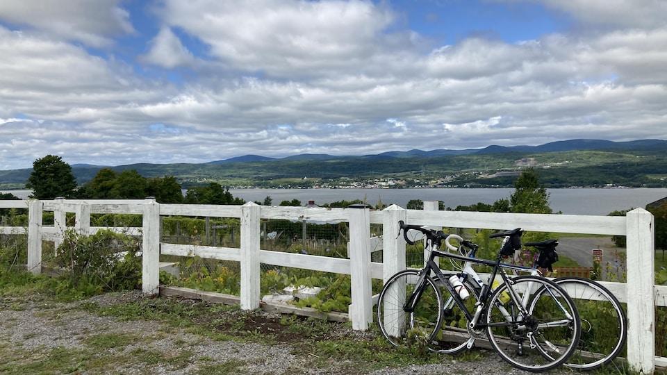 Des vélos accotés sur une clôture blanche devant une vue sur le fleuve.