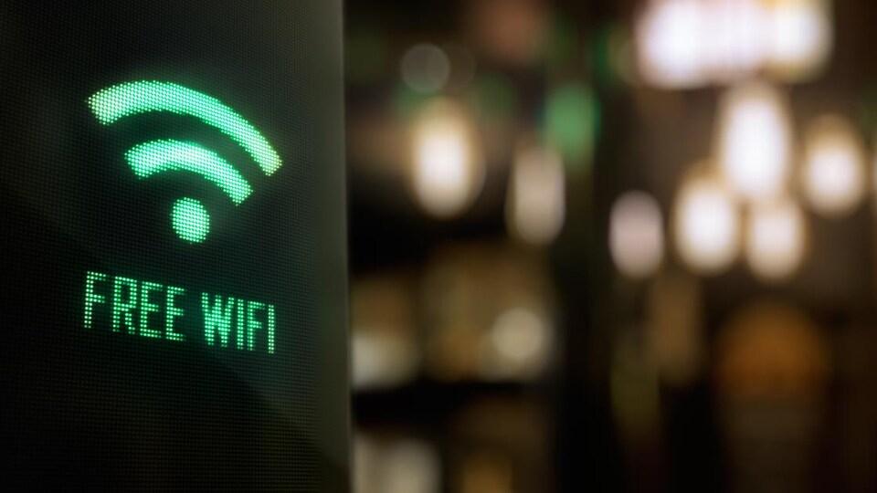 Un affichage lumineux vert sur un écran noir affiche la mention « free wifi » (wifi gratuit).