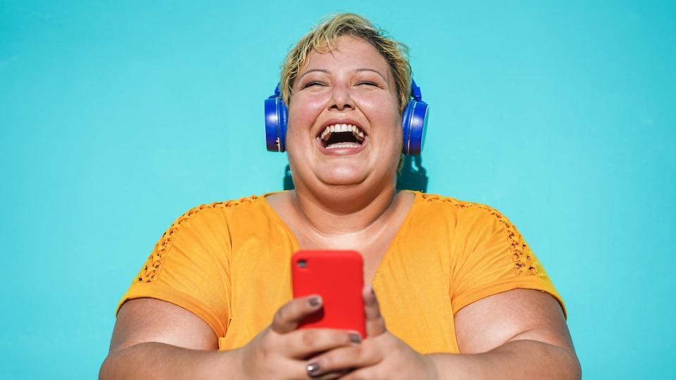 Une femme écoute du contenu de son téléphone cellulaire dans ses écouteurs sans fil.