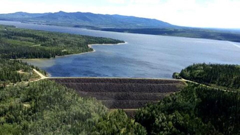 Des forêts et un lac, avec un barrage au centre, des montagnes en arrière-plan.
