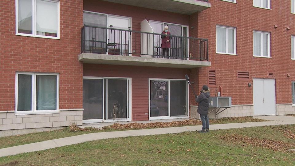 Un journaliste de Radio-Canada tend un micro accroché à une perche vers une résidente qui lui parle depuis son balcon. Tous les deux portent le masque.