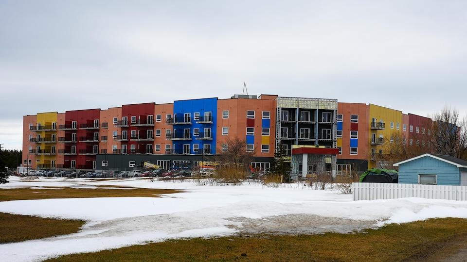 Un édifice massif multicolore avec de nombreux balcons.