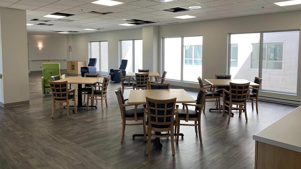 Plusieurs tables et des chaises sont disposées dans un salon lumineux.