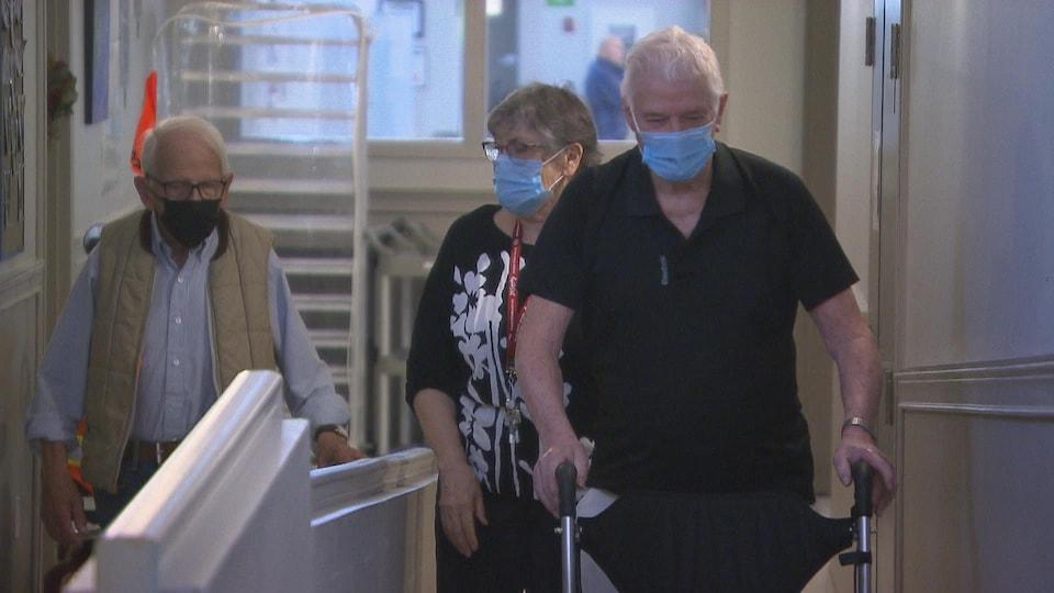 Des résidents portent le masque lors de leur déplacement dans un couloir de leur résidence.