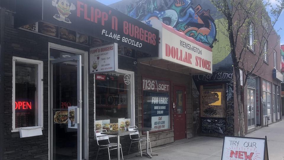 Devanture du restaurant Flipp'n Burgers.  Il y a à côté de la porte à l'extérieur une petite table avec deux chaises. Sur la fenêtre, il y a des affiches de hamburgers.