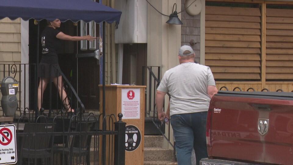 Un couple s'apprête à rentrer dans un restaurant. Une serveuse tient la porte ouverte.