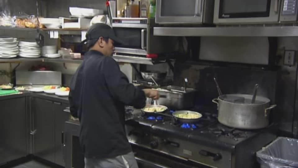 Un cuisinier prépare des plats dans un restaurant