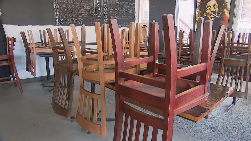 Des chaises installées sur des tables dans un restaurant fermé.