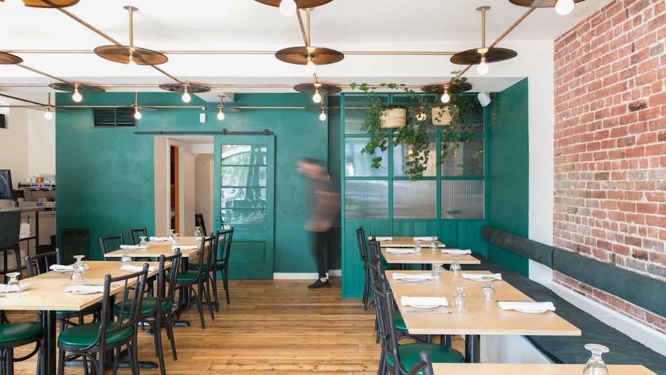 L'intérieur d'un restaurant avec des tables, des chaises, des plantes et un mur en briques.