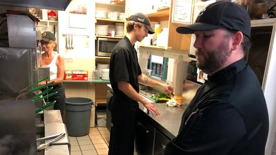 Trois personnes travaillent dans un restaurant.