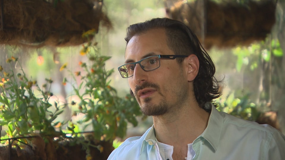 Shea Ritchie est debout sur la terrasse de son restaurant. Il porte des lunettes et une chemise. Derrière lui se trouvent des plantes et des fleurs.