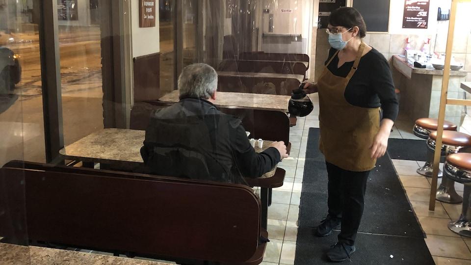 Une serveuse verse un café à un client.
