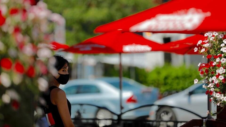 Une femme avec un masque sur la terrasse d'un restaurant.