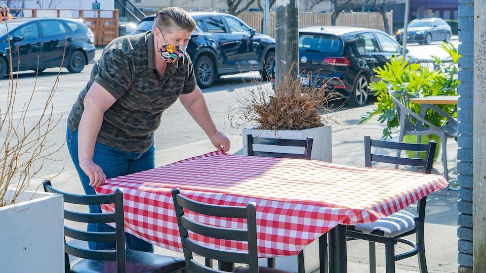 Une employée du restaurant torontois Gio Rana's Really Really Nice dresse une table sur une terrasse.