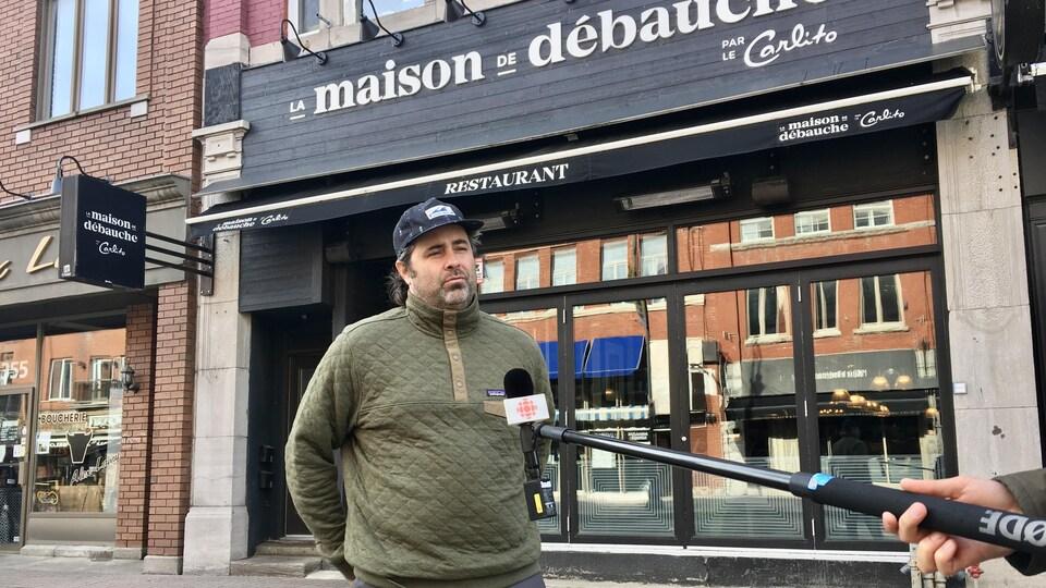 Un homme sur la rue, devant la vitrine de son restaurant, parle au micro d'un journaliste.