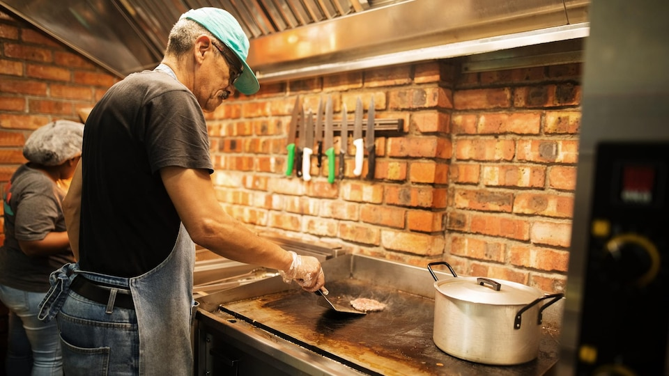 Un cuisinier faire cuire une boulette de boeuf haché.