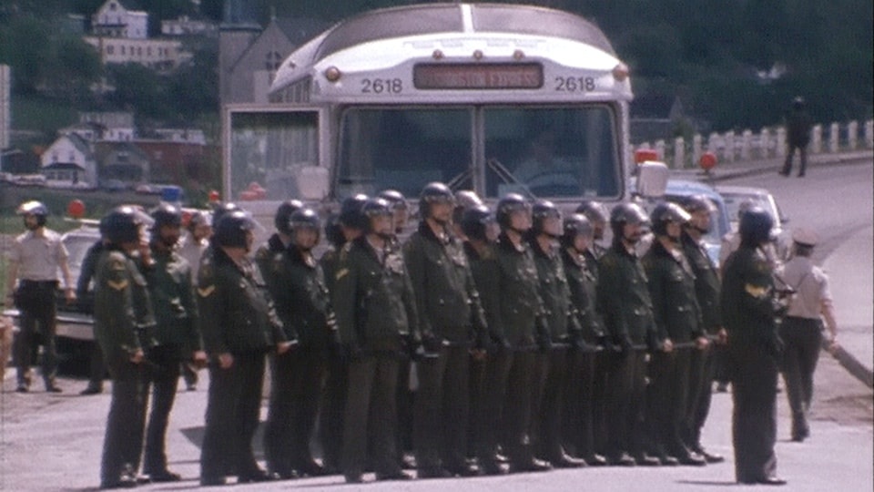 Des policiers en rang devant un autobus, le 11 juin 1981.