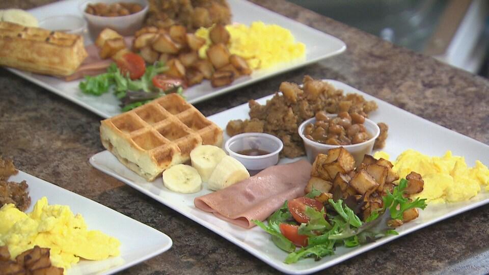 Une assiette contient de la tourtière, des oeufs, des patates, des fèves au lard, du jambon et un gaufre.