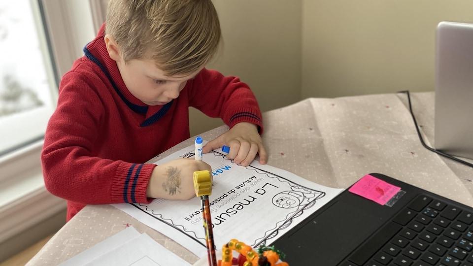 Un enfant habillé d'un chandail rouge écrit son nom sur une feuille installée devant un ordinateur portable.