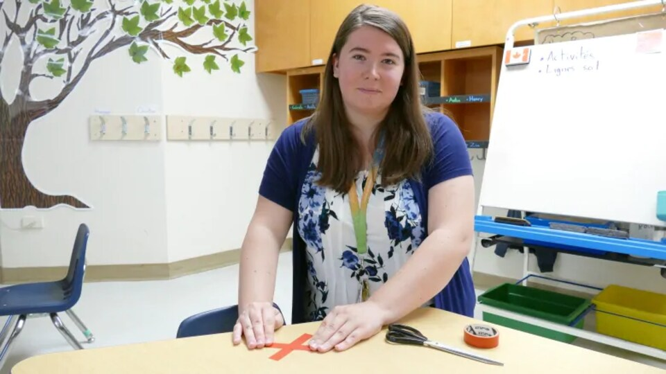Une enseignante dans sa classe a mis une croix rouge sur une table.