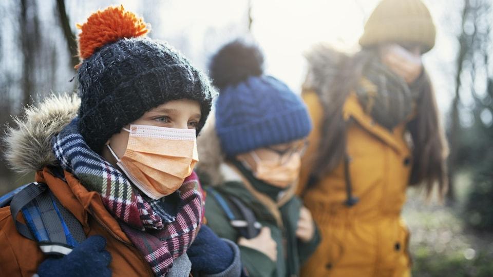 Trois jeunes d'âges différents marchent vers l'école avec des sacs à dos. Ils portent chacun un masque non médical et sont habillés pour le temps froid avec un manteau et une tuque.