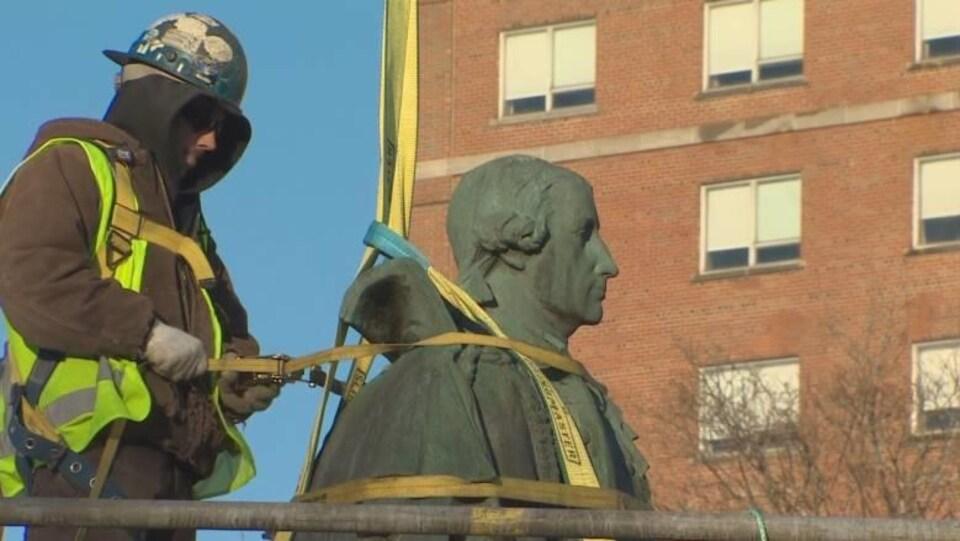 Un employé de la ville retire la statue d'Edward Cornwallis du parc du même nom, à Halifax.