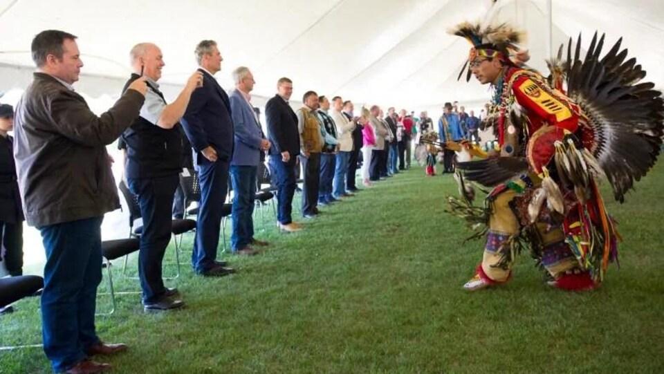 Un homme habillé en tenue traditionnelle de pow-wow danse devant les dirigeants alignés face à lui.