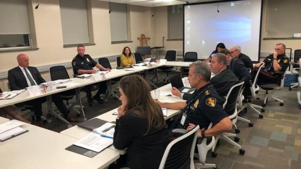 Une dizaine de personnes, dont des policiers, participent à une réunion dans une salle de conférence.