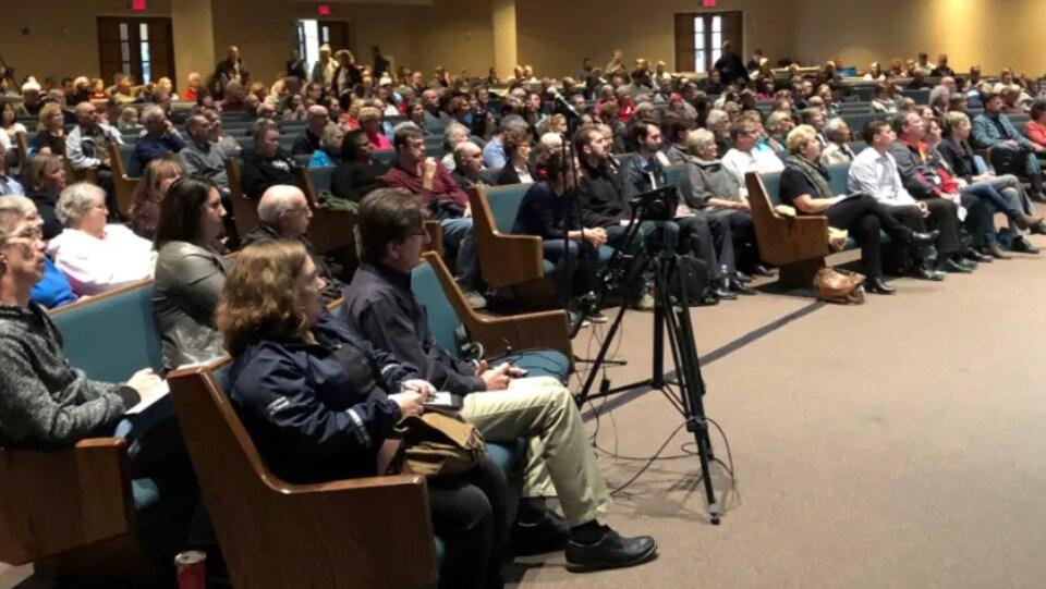 Des centaines de personnes rassemblées pour une séance d'information à l'intérieur d'une église.