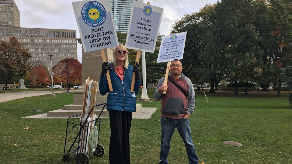Deux manifestants avec des pancartes.