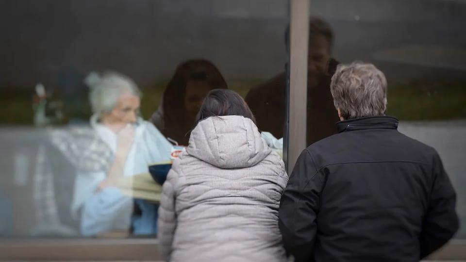 Un couple vu de dos regarde une aînée à travers une vitre.