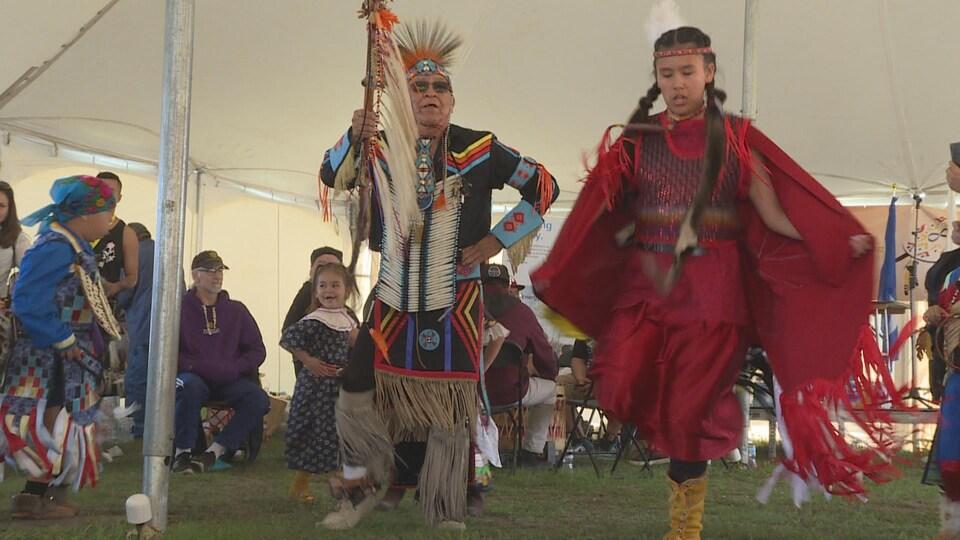 Un homme et un enfant dansent durant un pow-wow.
